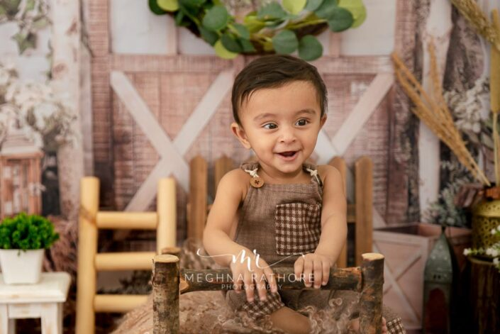 9 months old baby boy wearing adorable brown outfit sitting and posing with forest theme based professional photoshoot at meghna rathore photography in noida