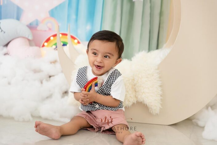 9 months old baby boy wearing adorable outfit sitting and posing smiling with theme based professional photoshoot at meghna rathore photography in noida
