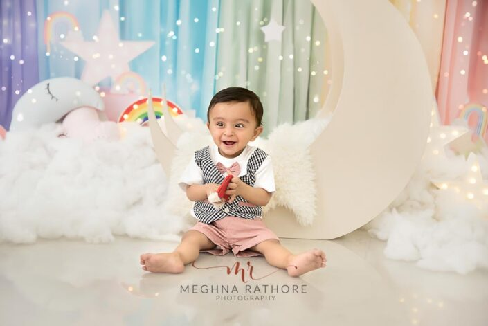 9 months old baby boy wearing cute outfit sitting and smiling with theme based professional photoshoot at meghna rathore photography in noida