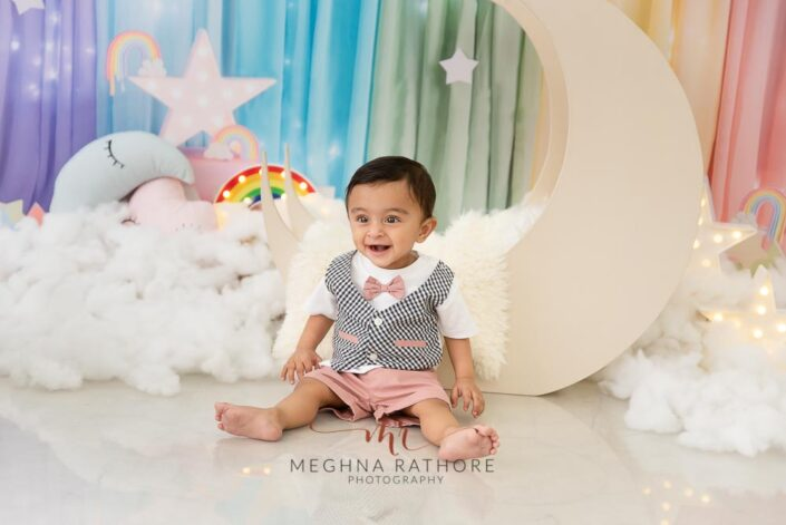 9 months old baby boy wearing cute outfit sitting and posing with sky theme based professional photoshoot at meghna rathore photography in noida