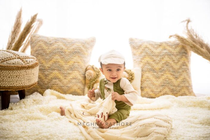 9 months old baby boy wearing cute outfit sitting and posing with theme based professional photoshoot at meghna rathore photography in noida