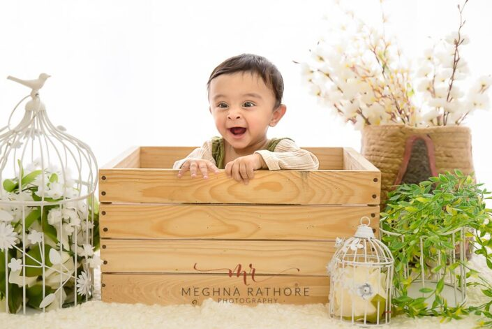 9 months old baby boy sitting inside a wooden box and smiling with theme based professional photoshoot at meghna rathore photography in noida