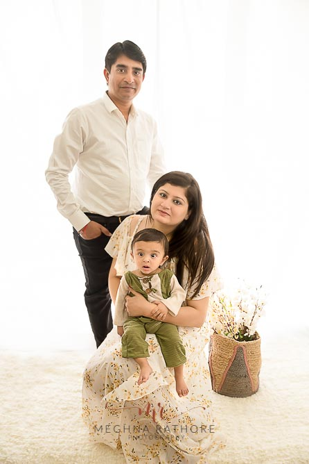 Family portrait of 9 months old boy and his parents wearing white colored outfit at meghna rathore photography in noida