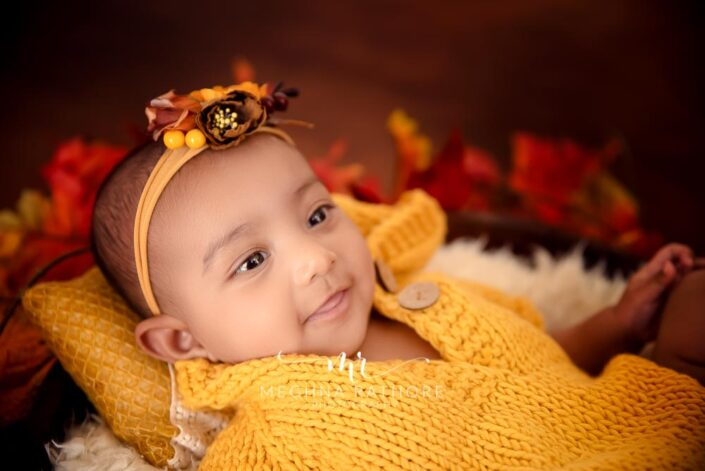 Baby girl posing at professional photoshoot with autumn themed props at meghna rathore photography in delhi and gurgaon