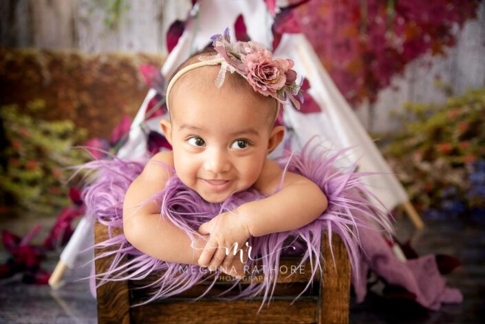 Baby girl smiling with a flower hairband over her head and posing at meghna rathore photography in delhi and gurgaon