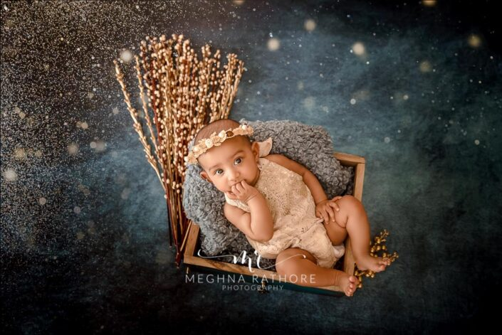 Baby girl looking curiously with a tiara over her head and posing inside a basket at meghna rathore photography in delhi and gurgaon