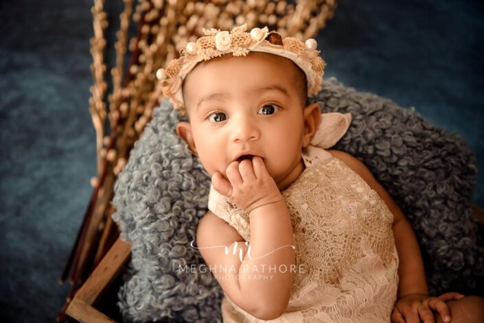 Baby girl looking curiously with a tiara over her head and posing at meghna rathore photography in delhi and gurgaon