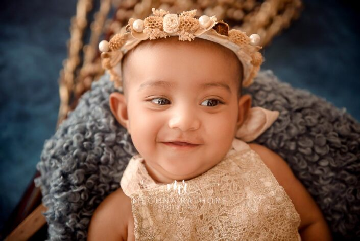 Baby girl smiling with a tiara over her head and posing at meghna rathore photography in delhi and gurgaon