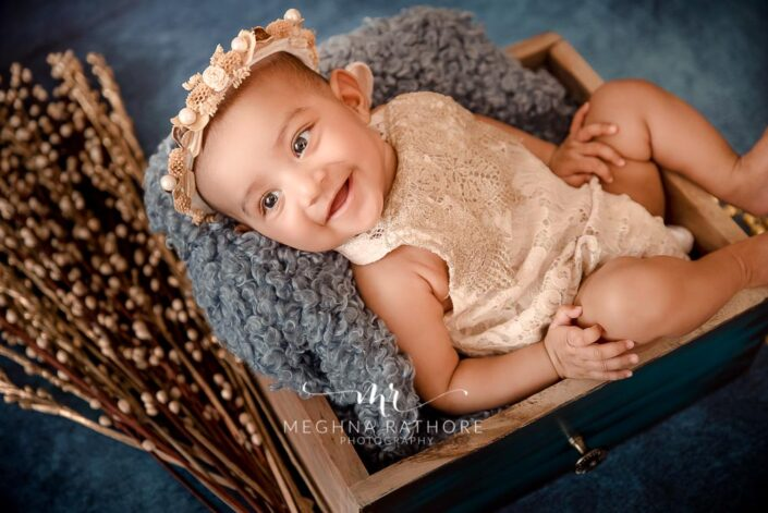 Baby girl smiling and posing for a professional photoshoot at meghna rathore photography in delhi gurgaon