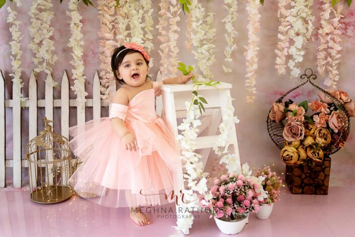 1 year old girl posing standing against a ladder for professional photoshoot at meghna rathore photography in delhi gurgaon