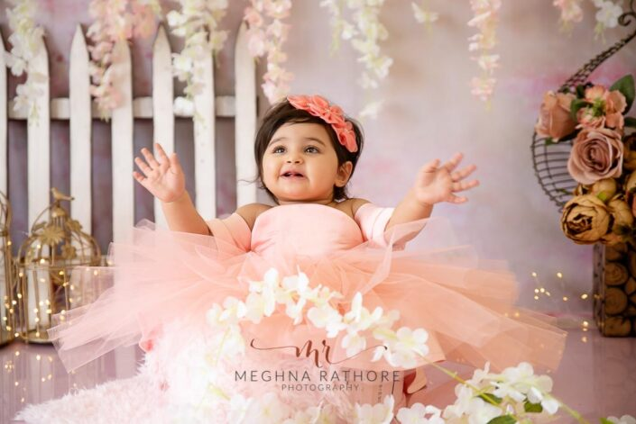1 year old girl posing and smiling candidly for professional photoshoot at meghna rathore photography in delhi gurgaon
