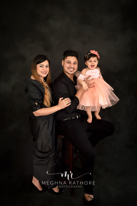 Family portrait with one year old baby girl all posing and smiling at meghna rathore photograhy in delhi gurgaon