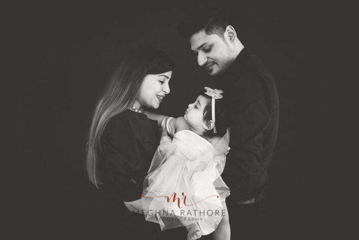 Black and white family portrait with one year old baby girl all posing at meghna rathore photograhy in delhi gurgaon