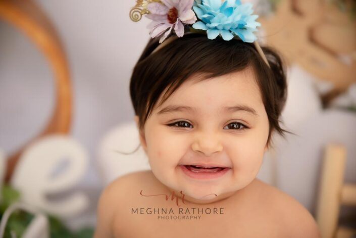 1 year old baby girl close up shot with flower hairband over her head and posing at meghna rathore photography in delhi gurgaon