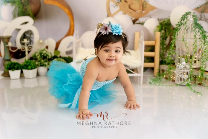 1 year old girl posing in a blue colored frock and crawling for professional photoshoot at meghna rathore photography in delhi gurgaon