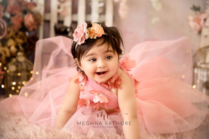 1 year old girl posing in a pink frock and smiling candidly for professional photoshoot at meghna rathore photography in delhi gurgaon
