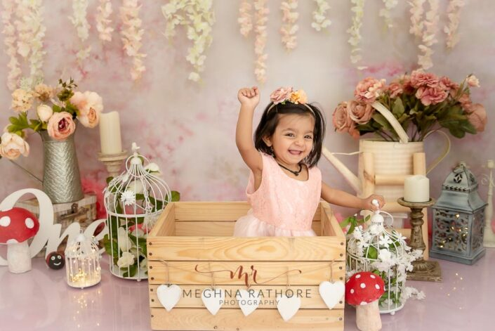 1 year old cute girl photo shoot poses smiling brightly inside a wooden box indoor photoshoot for meghna rathore photography in delhi gurgaon