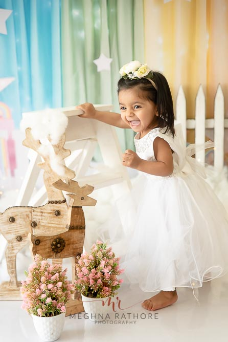 1 year old cute girl photo shoot poses smiling brightly in white frock for meghna rathore photography in delhi gurgaon