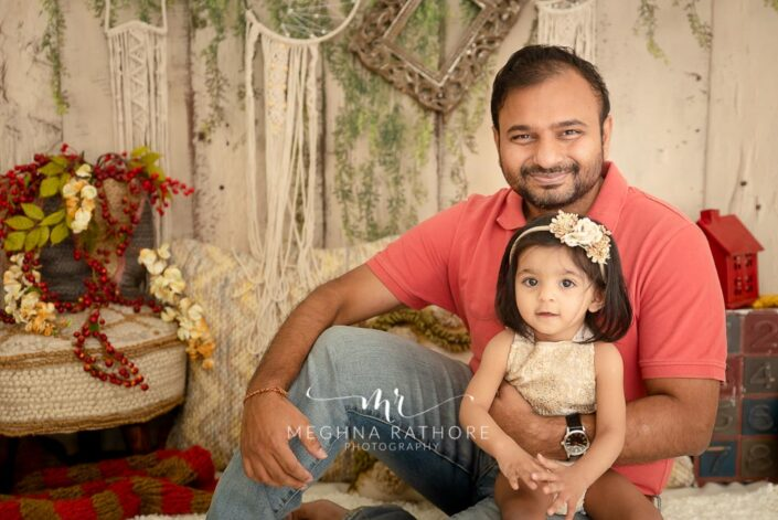 Family portrait of father and baby girl sitting and posing together at meghna rathore photography in delhi gurgaon