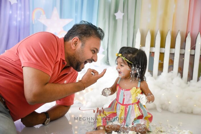 1 year old baby girl cake smash with father beside her posing professional photoshoot at meghna rathore photography in delhi gurgaon