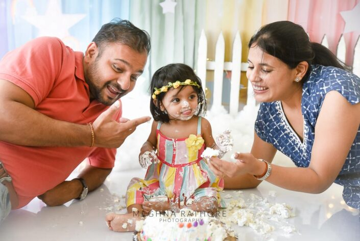 1 year old baby girl cake smash with parents beside her posing professional photoshoot at meghna rathore photography in delhi gurgaon