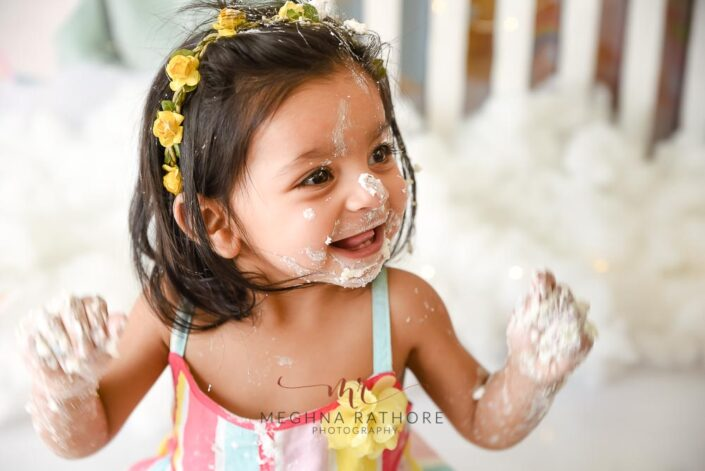 1 year old baby girl cake smash face covered with cake professional photoshoot at meghna rathore photography in delhi gurgaon