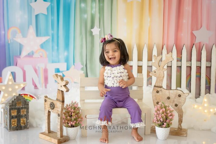 1 year old cute girl photo shoot poses smiling brightly with different props around her for meghna rathore photography in delhi gurgaon