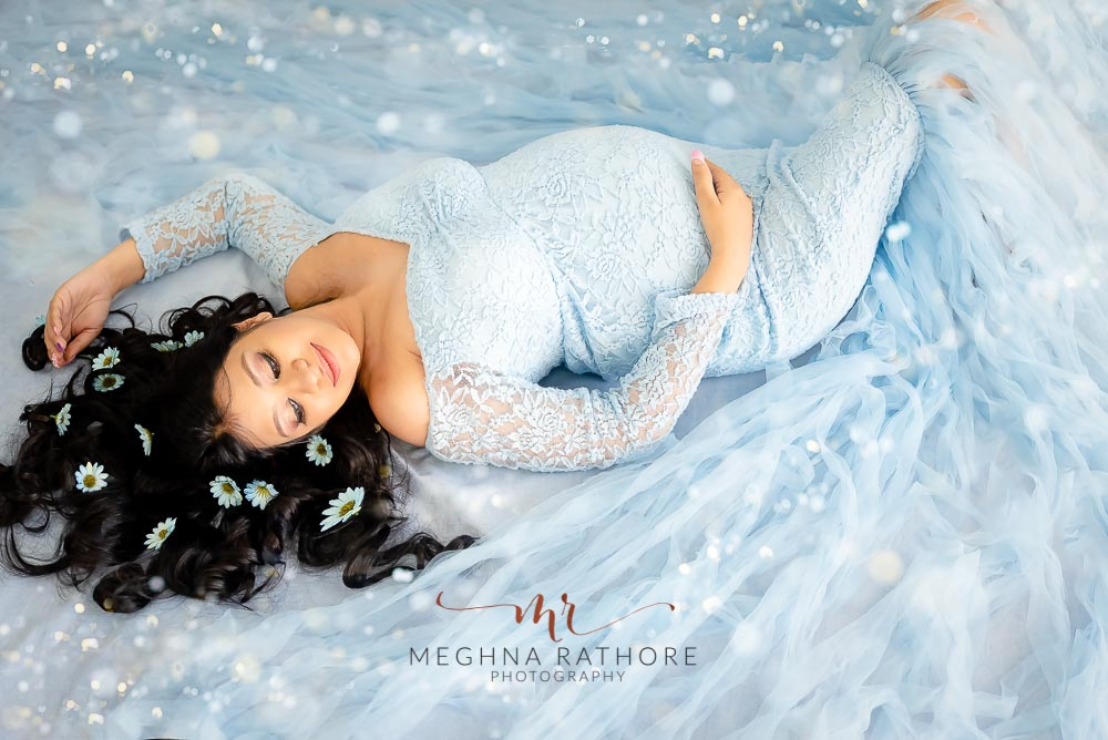 delhi professional maternity photo shoot by meghna rathore photography expecting mother in blue dress lying on floor and posing
