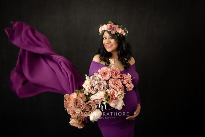 Maternity professional photoshoot beautiful lady posing with flower bouquet in her hands at meghna rathore photography in delhi gurgaon