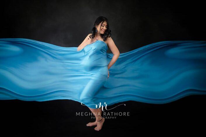 Maternity professional photoshoot lady posing and smiling in a blue cloth covered on her at meghna rathore photography in delhi gurgaon