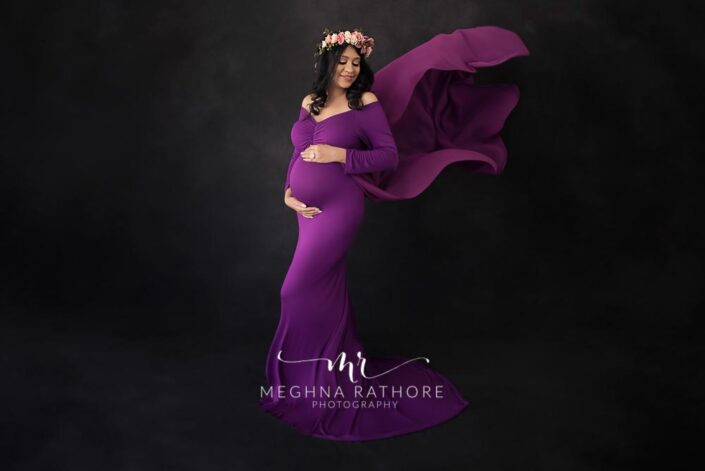 Maternity professional photoshoot lady posing in a beautiful violet colored gown and flower tiara over her head at meghna rathore photography in delhi gurgaon