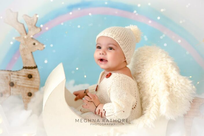 6 months old baby boy wearing adorable white colored outfit and props around him posing professional photoshoot at meghna rathore photography in noida