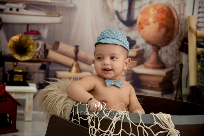 6 months old baby boy posing with props around him and theme based professional photoshoot at meghna rathore photography in noida