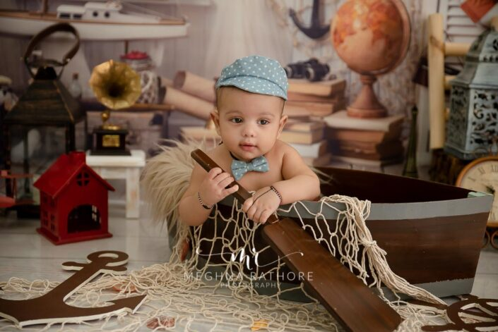 6 months old baby boy wearing cute outfit and props around him posing professional photoshoot at meghna rathore photography in noida