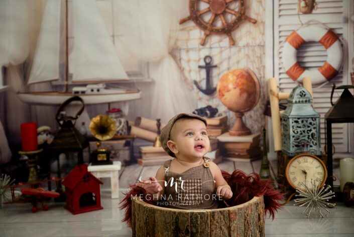 6 months old baby boy wearing brown colored outfit and props around him posing professional photoshoot at meghna rathore photography in noida
