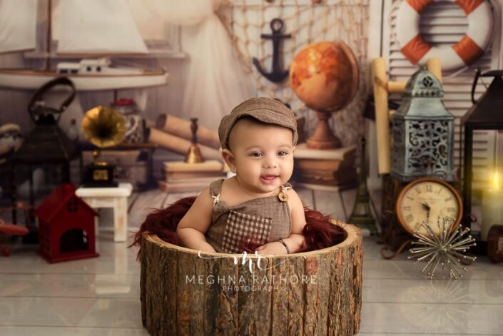 6 months old baby boy wearing brown colored outfit and posing inside a wooden trunk professional photoshoot at meghna rathore photography in noida