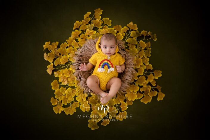 6 months old baby boy wearing yellow colored woolen outfit and leaves around him posing professional photoshoot at meghna rathore photography in noida