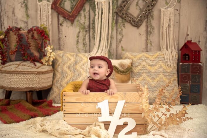 6 months old baby boy wearing red colored outfit sitting inside a wooden box and props around him posing professional photoshoot at meghna rathore photography in noida
