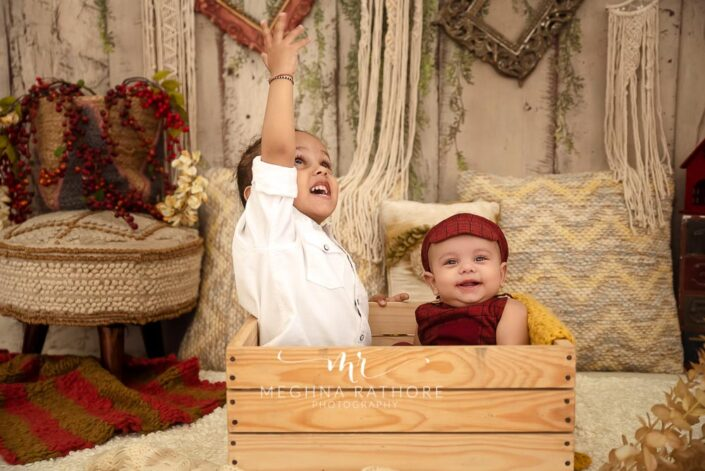 6 months old baby boy and his big brother posing with props around them professional photoshoot at meghna rathore photography in noida