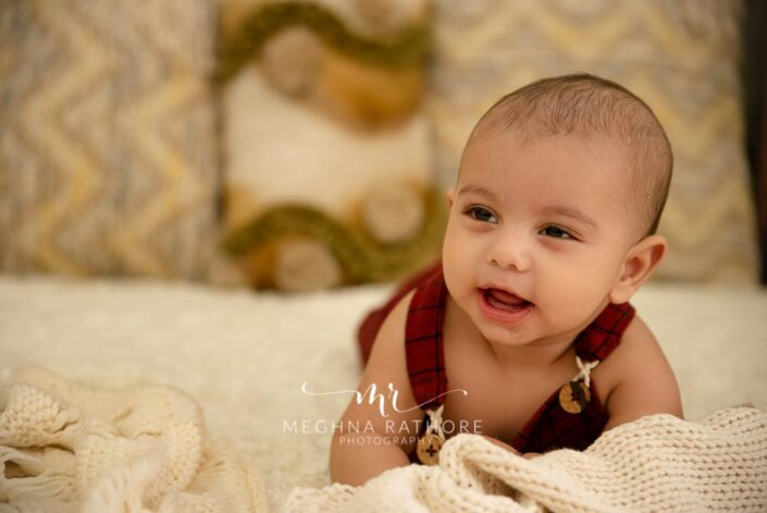 6 months old baby boy wearing red colored outfit and props around him posing professional photoshoot at meghna rathore photography in noida