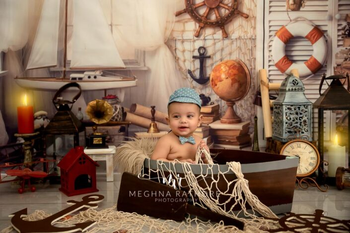 6 months old baby boy ship based theme and props around him posing professional photoshoot at meghna rathore photography in noida