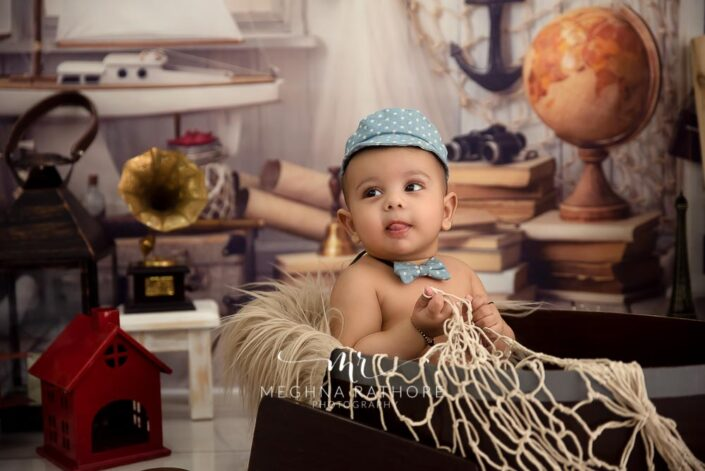 6 months old baby boy wearing bow and cute cap and props around him posing professional photoshoot at meghna rathore photography in noida