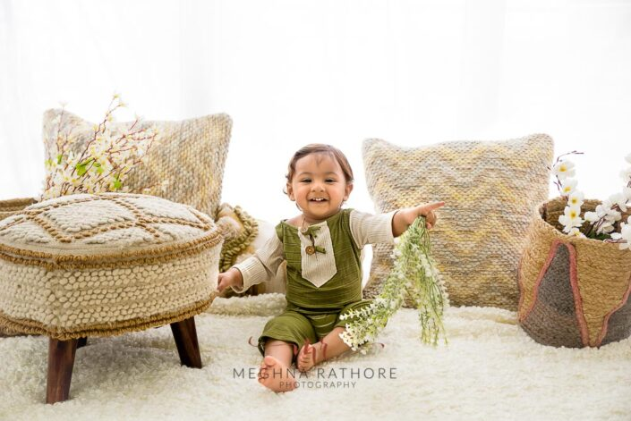 1 year old cute boy posing with flowers in hands indoor photoshoot at meghna rathore photography in delhi gurgaon