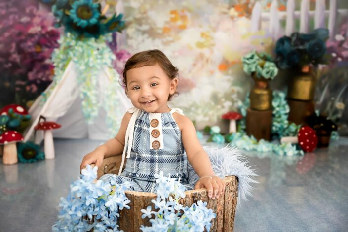 1 year old cute boy posing inside a wooden basket at meghna rathore photography in delhi gurgaon