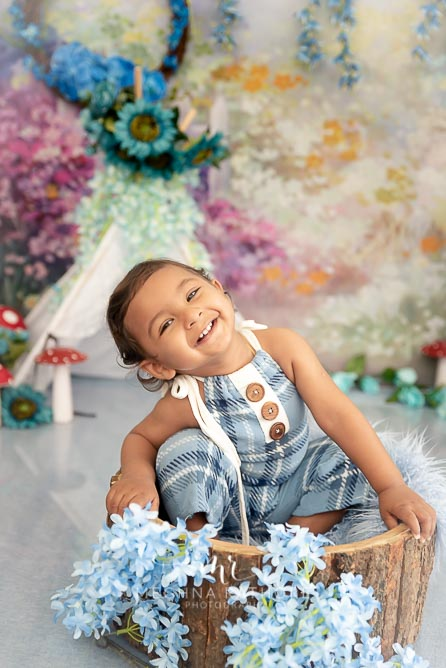 1 year old adorable boy posing inside a wooden basket at meghna rathore photography in delhi gurgaon