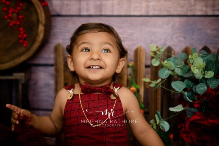 1 year old boy in red and green colored theme professional photoshoot at meghna rathore photography in delhi gurgaon