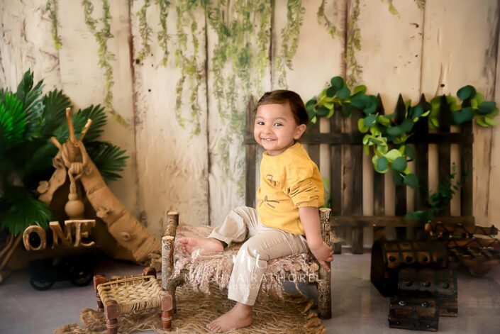 1 year old boy smiling and posing candid in a forest themed for professional photoshoot at meghna rathore photography in delhi and gurgaon