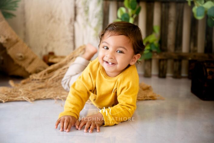 1 year old boy smiling and posing for professional photoshoot at meghna rathore photography in delhi and gurgaon