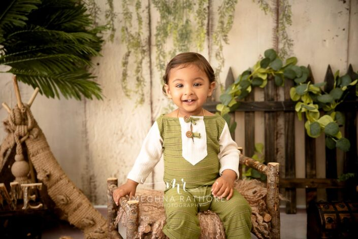 1 year old cute boy posing in green and white colored outfit at meghna rathore photography in delhi gurgaon