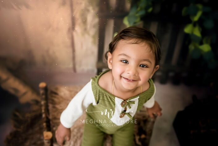 1 year old adorable boy posing in green and white colored outfit looking upwards at meghna rathore photography in delhi gurgaon